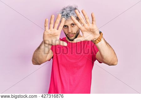 Young hispanic man with modern dyed hair wearing casual pink t shirt doing frame using hands palms and fingers, camera perspective