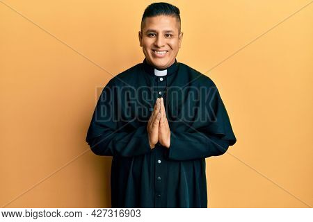 Young latin priest man praying with hands together smiling with a happy and cool smile on face. showing teeth.