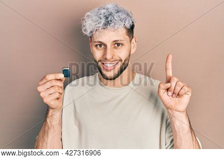 Young hispanic man with modern dyed hair holding sdxc card surprised with an idea or question pointing finger with happy face, number one