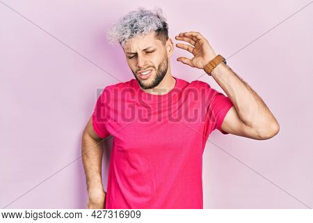 Young hispanic man with modern dyed hair wearing casual pink t shirt stretching back, tired and relaxed, sleepy and yawning for early morning