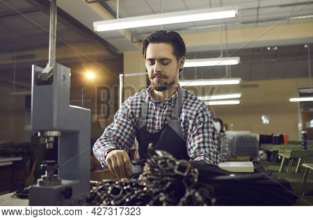 Young Focused Experienced Master Craftsman Makes Leather Belts At His Workplace.