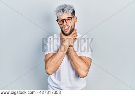 Young hispanic man with modern dyed hair wearing white t shirt and glasses shouting suffocate because painful strangle. health problem. asphyxiate and suicide concept.