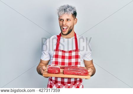 Young hispanic man with modern dyed hair holding board with raw meat angry and mad screaming frustrated and furious, shouting with anger. rage and aggressive concept.