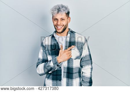 Young hispanic man with modern dyed hair wearing casual shirt cheerful with a smile of face pointing with hand and finger up to the side with happy and natural expression on face