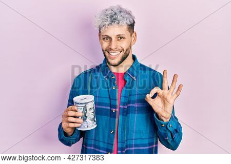 Young hispanic man with modern dyed hair holding piggy bank doing ok sign with fingers, smiling friendly gesturing excellent symbol
