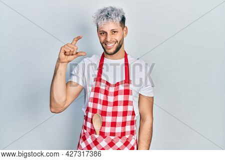 Young hispanic man with modern dyed hair wearing apron smiling and confident gesturing with hand doing small size sign with fingers looking and the camera. measure concept.