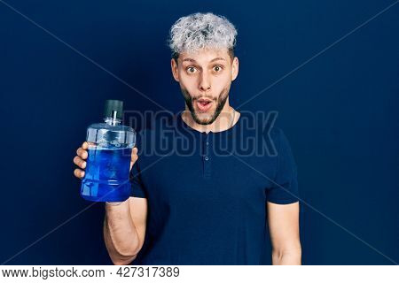 Young hispanic man with modern dyed hair holding mouthwash for fresh breath scared and amazed with open mouth for surprise, disbelief face