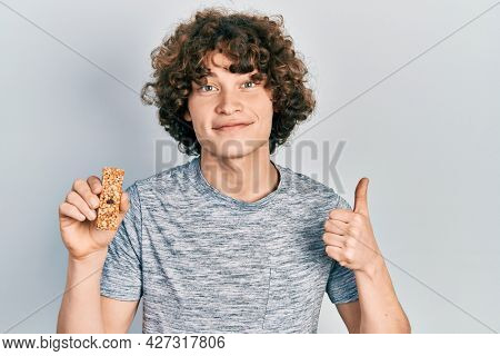 Handsome young man eating protein bar as healthy energy snack smiling happy and positive, thumb up doing excellent and approval sign