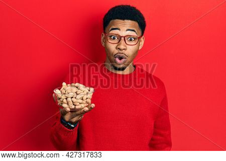 Young african american man holding peanuts scared and amazed with open mouth for surprise, disbelief face