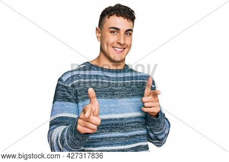 Hispanic young man wearing casual clothes pointing fingers to camera with happy and funny face. good energy and vibes.