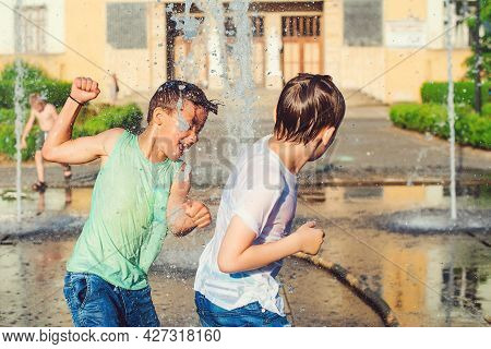 Boys Jumping In Water Fountains. Children Playing With A City Fountain On Hot Summer Day. Happy Frie