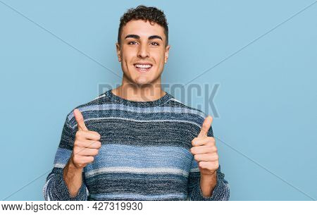 Hispanic young man wearing casual clothes success sign doing positive gesture with hand, thumbs up smiling and happy. cheerful expression and winner gesture.