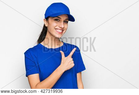 Young hispanic girl wearing delivery courier uniform cheerful with a smile of face pointing with hand and finger up to the side with happy and natural expression on face