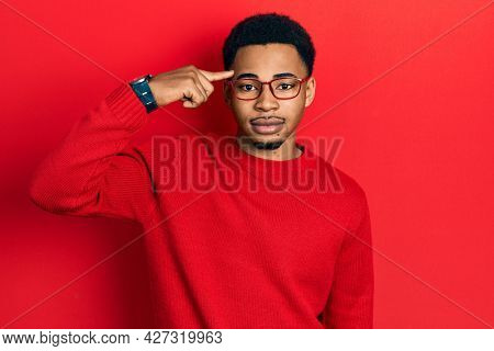 Young african american man pointing head with finger relaxed with serious expression on face. simple and natural looking at the camera.