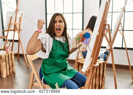 Young hispanic artist women painting on canvas at art studio angry and mad raising fist frustrated and furious while shouting with anger. rage and aggressive concept.