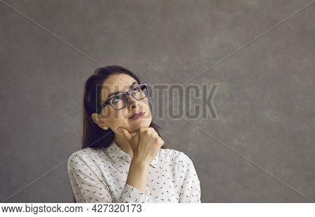 Thoughtful Young Caucasian Woman Touching Chin By Hand Studio Headshot