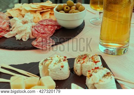 Typical Aperitif In Italian Style: Beer, Olives, Cold Cuts, Cheeses With Chilli And Honey, Breadstic