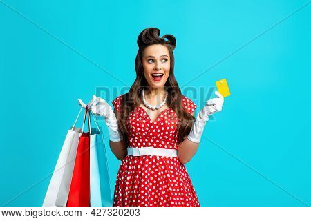 Joyful Pin Up Woman In Retro Outfit Holding Credit Card And Shopping Bags, Feeling Excited, Choosing