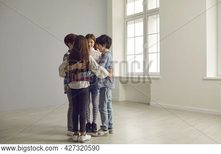 Little Group Of School Children Huddling Standing Together In Spacious Empty Room