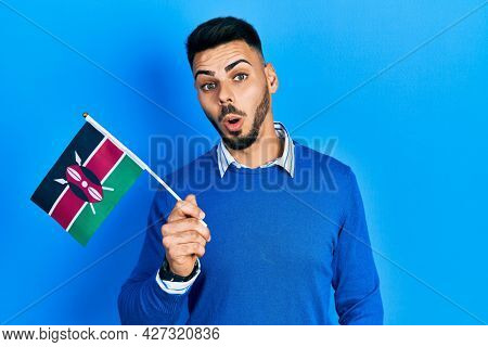 Young hispanic man with beard holding kenya flag scared and amazed with open mouth for surprise, disbelief face