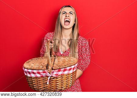 Beautiful hispanic woman holding picnic wicker basket angry and mad screaming frustrated and furious, shouting with anger looking up.
