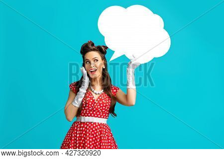 Young Pinup Woman In Retro Dress Holding Blank White Speech Bubble On Blue Studio Background. Empty