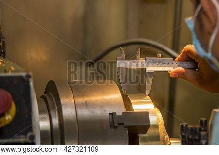 The Operator Measure Thickness Of Turning Brass Material Part By Vernier Caliper . The Metalworking