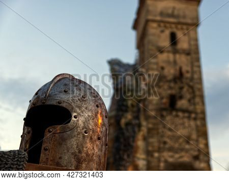 Close Up Of A Helmet Resting On A Chain Mail With A Romanesque Bell Tower In The Background. High Qu