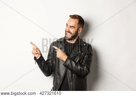 Confident Macho Man In Black Leather Jacket, Pointing Fingers Left At Promo Offer, Showing Logo, Whi