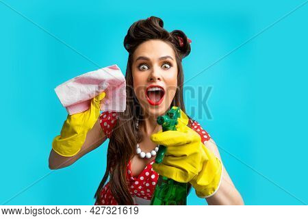 Crazy Young Pinup Housewife Wearing Retro Outfit And Rubber Gloves, Holding Spray Detergent And Rag