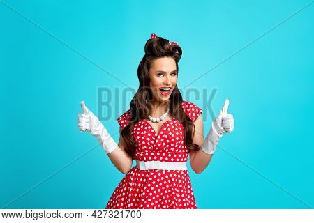 Overjoyed Young Pinup Woman In Retro Outfit Showing Thumbs Up Gesture, Widely Smiling Over Blue Stud