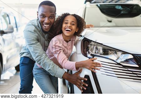 Happy Black Father And His Cute Daughter Selecting New Car, Buying Or Renting Automobile At Auto Dea