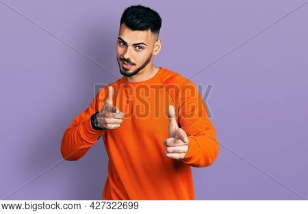 Young hispanic man with beard wearing casual orange sweater pointing fingers to camera with happy and funny face. good energy and vibes.