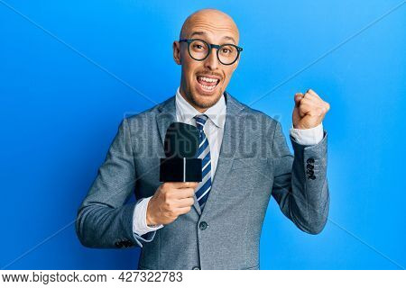 Bald man with beard holding reporter microphone screaming proud, celebrating victory and success very excited with raised arm