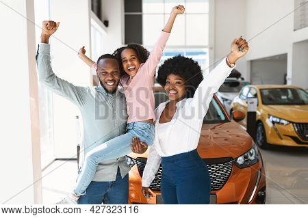 Excited Black Family Of Three Lifting Hands Up, Celebrating New Car Purchase In Auto Dealership
