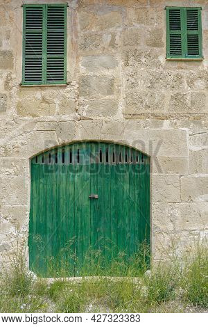Facade Of An Old Farm. Door And Windows Of Natural Wood Texture, Stone Walls Of Mares, Typical Natur