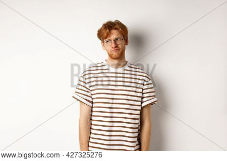 Sad And Gloomy Redhead Man Looking Upper Left Corner, Sulking And Feeling Like Loser, Standing Over