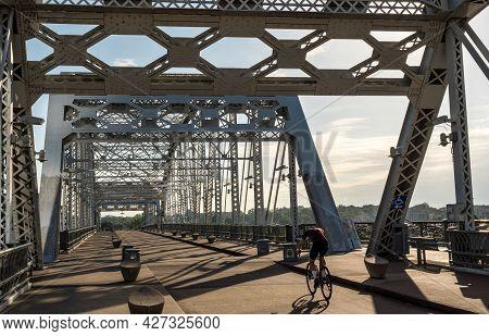 Cyclist On The John Seigenthaler Pedestrian Bridge Or Shelby Street Crossing Leaving Downtown Nashvi