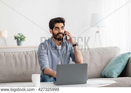 Freelance Lifestyle. Arab Man Using Laptop And Talking On Cellphone, Working While Sitting On Sofa I