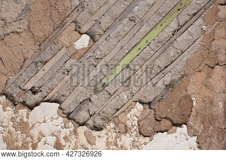 Fragment Of An Old Destroyed Wall With Fallen Off Plaster And Wooden Lath In Abandoned House. Close-