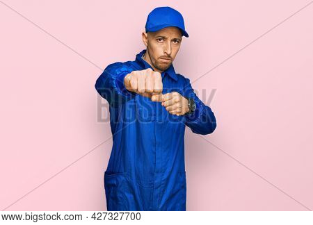 Bald man with beard wearing builder jumpsuit uniform punching fist to fight, aggressive and angry attack, threat and violence