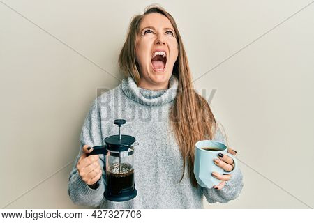 Young blonde woman drinking a cup of italian coffee angry and mad screaming frustrated and furious, shouting with anger looking up.