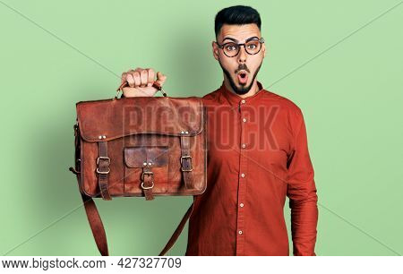 Young hispanic man with beard wearing leather bag scared and amazed with open mouth for surprise, disbelief face