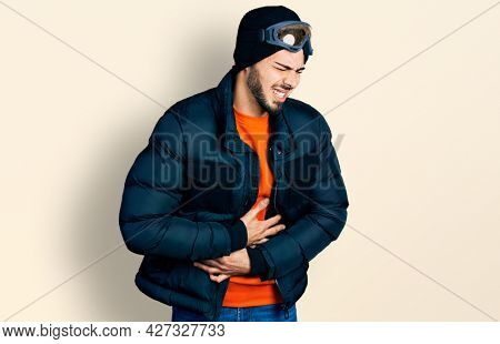 Young hispanic man with beard wearing snow wear and sky glasses with hand on stomach because nausea, painful disease feeling unwell. ache concept.