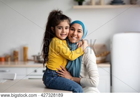 Happy Muslim Mother In Hijab And Little Daughter Posing In Kitchen Interior