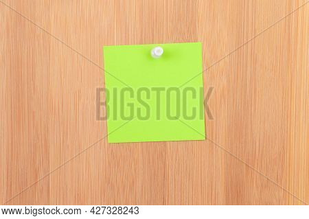 Green Sticky Note Pinned To The Wooden Message Board. To Do List Reminder In Office. Blank Memo Stic