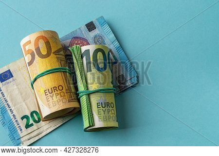 Green Roll Of 100 Euro Banknotes And Orange Roll Of 50 Euro Bills Over 20 Euro Paper Money Against B