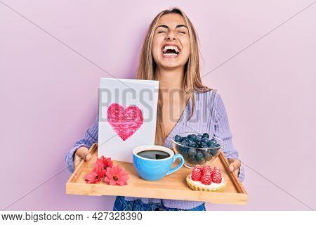 Beautiful hispanic woman holding tray with breakfast and heart card angry and mad screaming frustrated and furious, shouting with anger looking up.