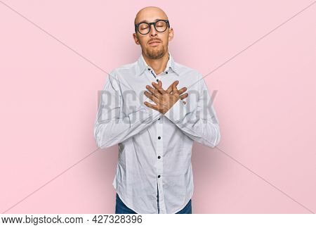 Bald man with beard wearing business shirt and glasses smiling with hands on chest with closed eyes and grateful gesture on face. health concept.
