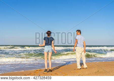 Man And Woman Standing On Sand Beach Of Sea Coast Against Stormy Waves In Sunny Summer Day. People S